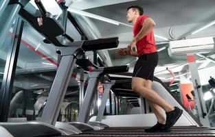 jeune homme athlétique courir et écouter de la musique à partir de son smartphone dans la salle de sport photo