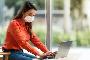 Femme portant un masque de protection à l'aide d'un ordinateur portable au café photo