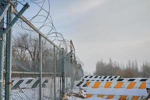 Clôture en fil de fer barbelé à la frontière avec des barrages routiers en béton au sol en hiver photo