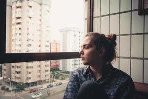 femme inquiète à la recherche de la fenêtre de son appartement photo