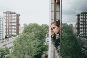 femme inquiète près de la fenêtre dans la ville pendant une journée de printemps photo