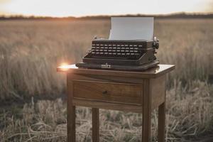 Machine à écrire sur une table de chevet en noyer dans un champ de blé au coucher du soleil photo
