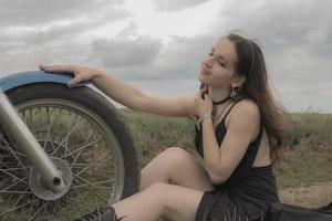 Biker brune sur une moto dans un champ de lavande contre le ciel avec des nuages au ralenti photo