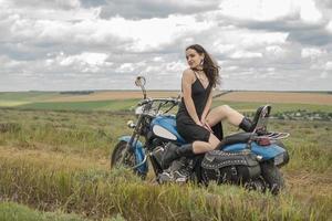 Biker brune sur une moto en veste de cuir noir champ de lavande contre le ciel avec des nuages au ralenti photo