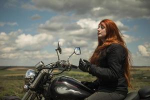 La fille de motard aux cheveux rouges est assise sur un champ de moto de prairie et de nuages photo
