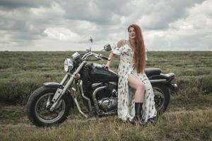 Fille aux cheveux rouges dans une robe blanche et des bottes avec un champ de lavande moto photo