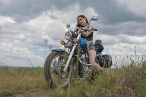 Biker brune sur une moto en veste de cuir noir champ de lavande contre le ciel avec des nuages photo