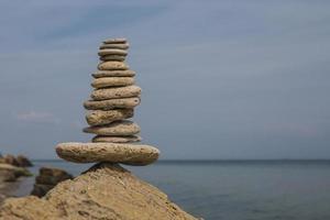 Pyramide de pierres en équilibre sur une grosse pierre au bord de la mer photo