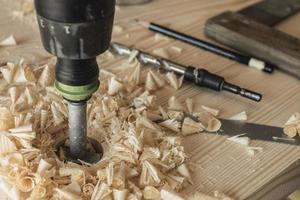 le menuisier perce une pièce de bois avec une perceuse photo