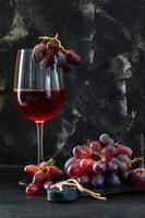 Verre de vin avec des raisins sur un support en bois noir photo
