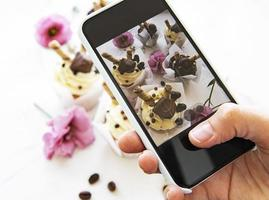 fille fait une photo de petits gâteaux sur un smartphone