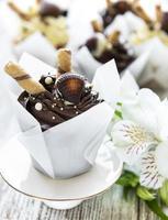 Petits gâteaux au chocolat sur fond de bois blanc photo
