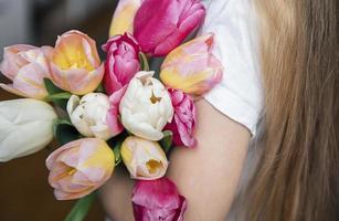 tulipes de printemps entre les mains d'une petite fille. photo