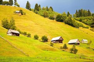 Paysage de montagne à moeciu de sus, Roumanie avec cabanes en bois sur les collines verdoyantes photo