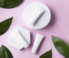 tubes blancs de crème sur fond rose photo