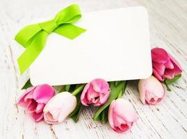 Tulipes roses et jaunes avec une carte sur un fond en bois blanc photo