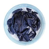 Blue jeans avec détergent liquide dans le bassin en plastique isolé sur fond blanc photo