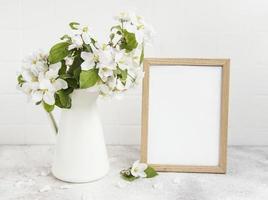 fleur de pommier de printemps dans un vase avec un cadre photo vide
