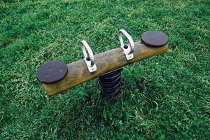 vieille balançoire en bois dans l'aire de jeux photo