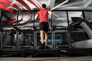 jeune homme athlétique courant dans la formation de remise en forme de sport de gym photo