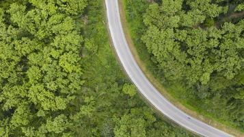 Vue aérienne de dessus d'une route provinciale passant à travers un fond de forêt photo