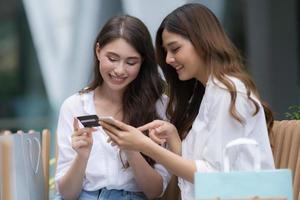 heureuse jeune femme avec un visage souriant parlant et riant tenant une carte de crédit et utilisant un téléphone photo