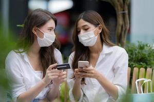 jeune femme portant un masque protecteur parlant et riant tenant une carte de crédit et utilisant un téléphone photo