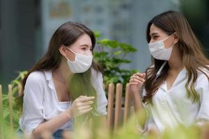 heureux deux jeunes femme avec un visage souriant portant un masque protecteur parlant et riant photo