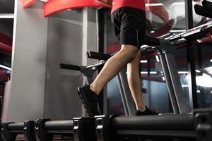 gros plan sur des jambes masculines s'exécutant sur un tapis roulant dans un concept de personnes de style de vie photo