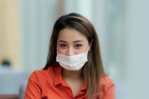 Portrait de jeune femme portant un masque protecteur assis dans un café photo