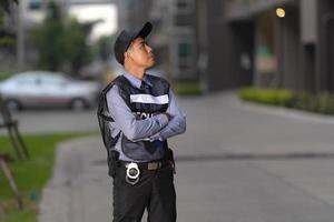 homme de sécurité debout à l'extérieur près d'un grand bâtiment photo