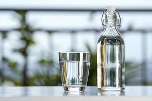 boire une bouteille d'eau avec un verre sur la table à la maison de jardin photo