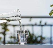verser de l'eau potable de la bouteille dans le verre à la maison de jardin photo