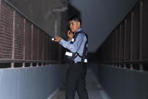 homme de sécurité debout à l'extérieur à l'aide d'une radio portable photo
