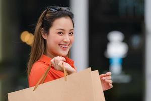 portrait en plein air de femme heureuse tenant des sacs à provisions photo