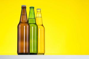 Groupe de trois bouteilles de bière isolé sur fond jaune photo