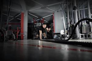 homme travaillant avec des cordes de combat au gymnase photo