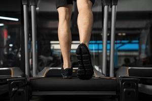 Close up of male jambes s'exécutant sur tapis roulant dans la salle de sport photo