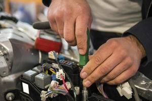 Un électricien automobile répare un testeur de voiture, des fusibles et des pinces photo