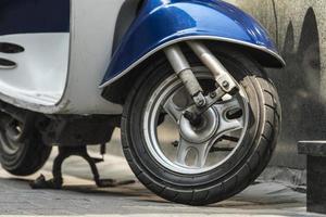 un cyclomoteur vintage avec une aile bleue est garé sur le trottoir papier peint scooter vintage photo