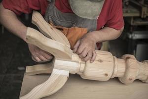 le menuisier fait une table avec des pieds sculptés photo