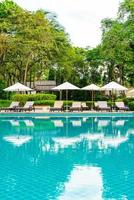 parasol et chaise autour de la piscine dans la station de l'hôtel photo