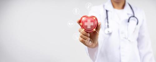 gros plan sur la main d'un médecin tenant un coeur rouge pour les maladies cardiaques, concept de service d'assurance maladie photo