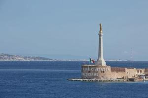 vue sur le port de messine avec la statue d'or de la madonna della lettera en sicile, italie photo