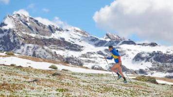 athlète de piste dans les montagnes en montée avec des bâtons photo