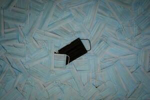 masque chirurgical noir sur fond de masques bleus photo