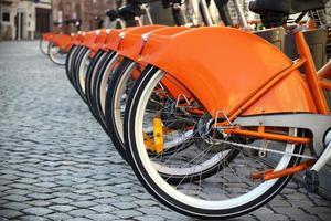 vélos de ville orange debout dans une rangée photo
