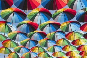 fond coloré de beaux parapluies contre le ciel bleu photo