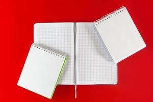 cahiers de fournitures de bureau sur fond rouge photo