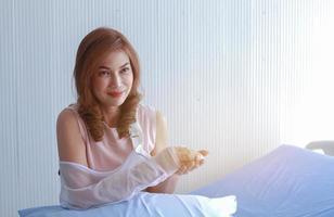 Une patiente victime d'un accident au bras cassé attendait de voir un médecin pour un traitement, elle était assise dans le lit d'hôpital photo